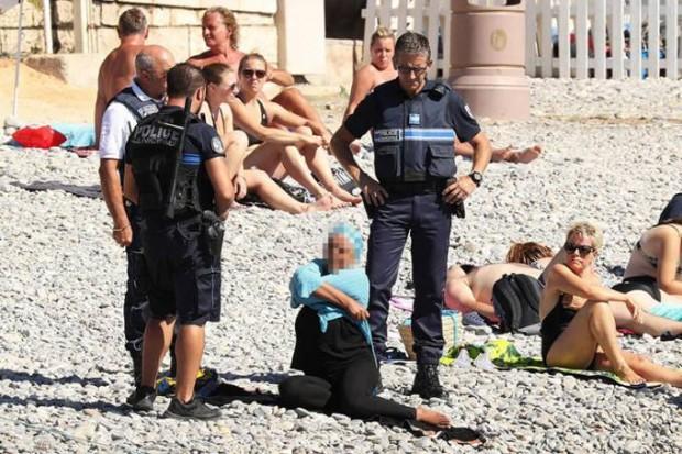 mundo-franca-praia-mulher-vestida-burca-policia-20160825-01